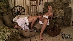 Two slender and horny blondes surrender their sexy bodies to one another in the barn