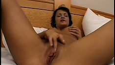 Cute brunette with lovely tits lies on the bed and takes a big dick deep in her twat
