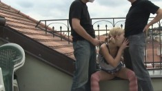 The terrace is a nice place for a threesome to pound this little blonde in masks