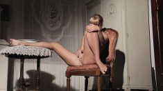 Delightful young blonde sits on a chair and gives it all to herself