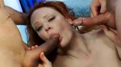 Nasty redhead with long legs has two horny guys stretching her holes
