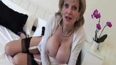 Naughty mature lady with big hooters lies on the bed and masturbates