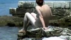 Naked Girl Walks On A Rocky Beach